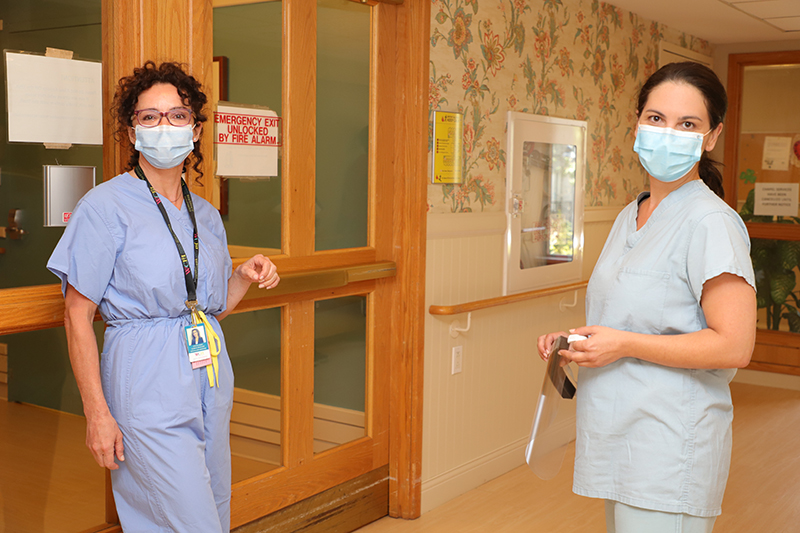 Two hospital staff members wearing PPE pose for the camera at Kensington Gardens Long Term Care Home