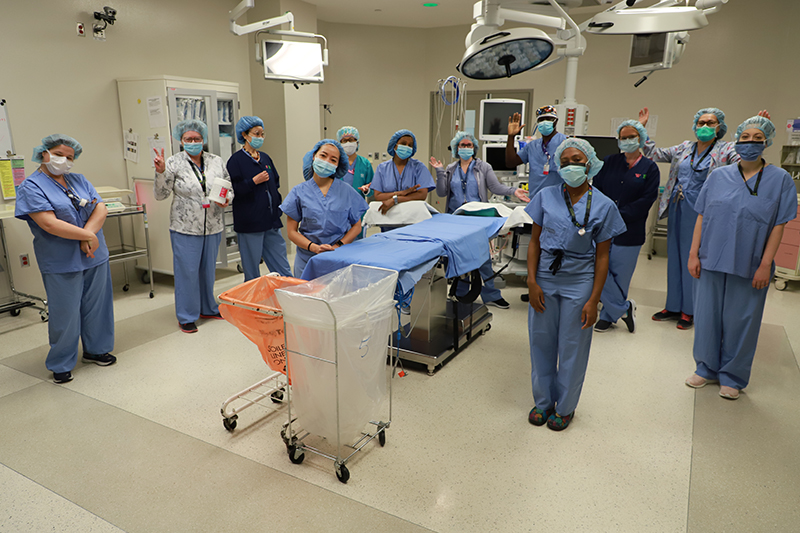 The AACU Surgical Unit team is gathered around an empty hospital bed