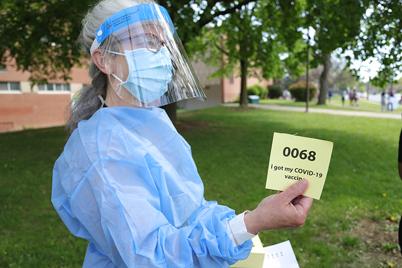 """A woman in full PPE gear holds a ticket that reads """"I got my COVID-19 Vaccine"""""""