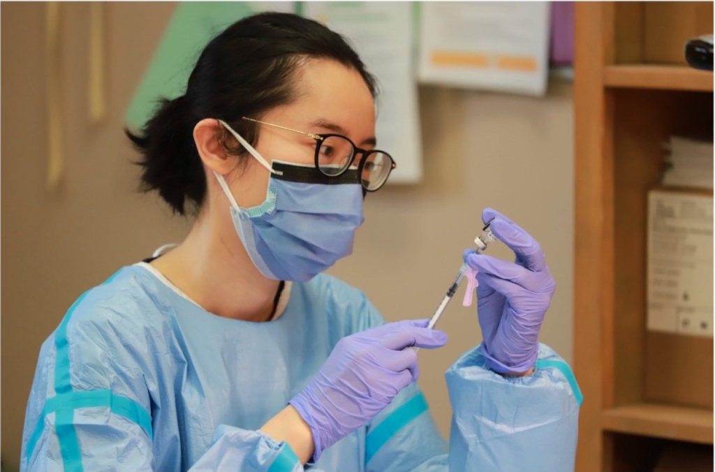 A healthcare working in PPE draws a vaccine.