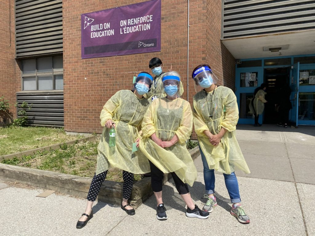 4 people in PPE pose in front of a school